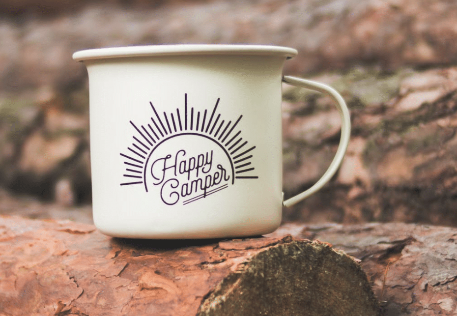 white happy camper printed cup on brown wooden