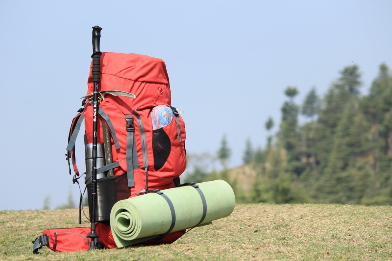 Red hiking backpack on green grass