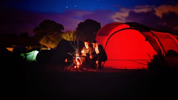 couple sitting beside tent