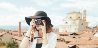 Girl holding the best travel camera is taking photos of the beautiful view that she saw