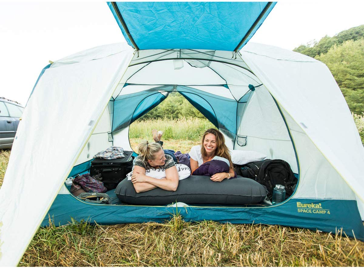 two woman inside a white and blue eureka tent